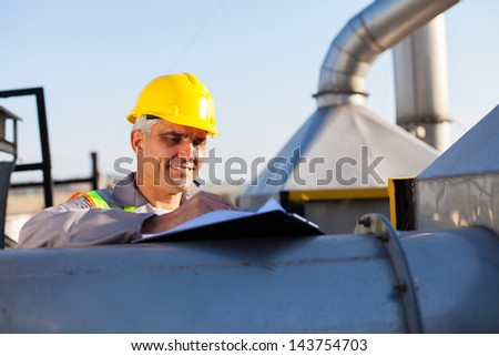 middle aged oil chemical industry technician working outdoors - stock photo