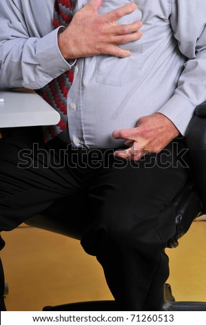 Middle aged,overweight man having a heart attack at his desk. Hand grasping his heart and pain radiating down his arm cramping his hand. - stock photo
