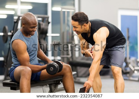 middle aged personal trainer training client in gym - stock photo