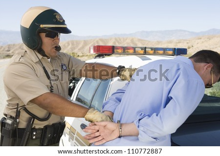 Middle aged policeman arresting a man on the road - stock photo