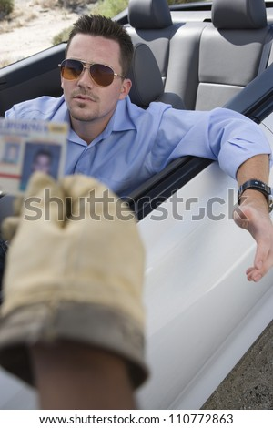 Middle aged policeman checking license of a young man - stock photo