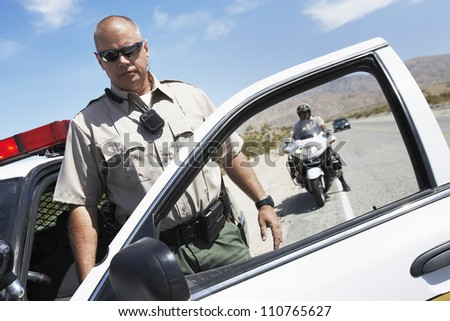 Middle aged policeman getting out from car - stock photo