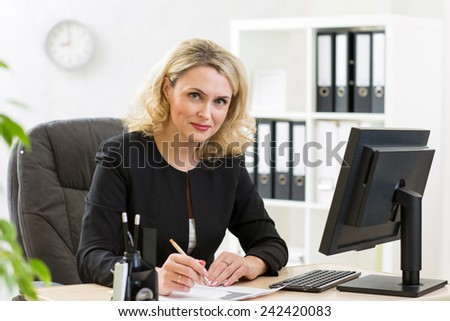 Middle-aged pretty business woman working at pc in office - stock photo