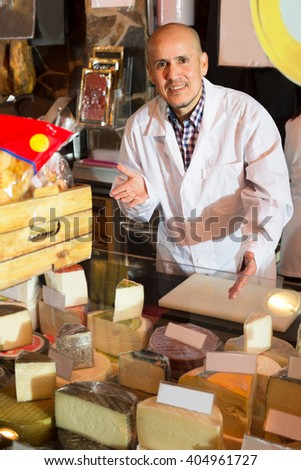 Middle aged salesman selling cheese and jamon in delicatessen section - stock photo
