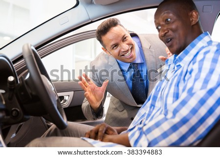 middle aged salesman showing new car interior to customer sitting inside the car - stock photo