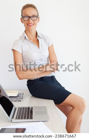 Middle aged senior office manager sitting and relaxing on desk at work, smiling confidently with her arms crossed and waring reading glasses. Professional businesswoman smiling in office, interior. - stock photo