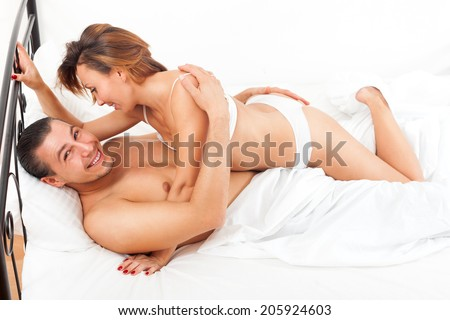 Middle-aged smiling couple kissing and playing on white sheet in bed at home - stock photo