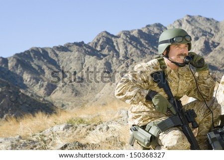 Middle aged soldier using telephone while holding rifle against mountain - stock photo