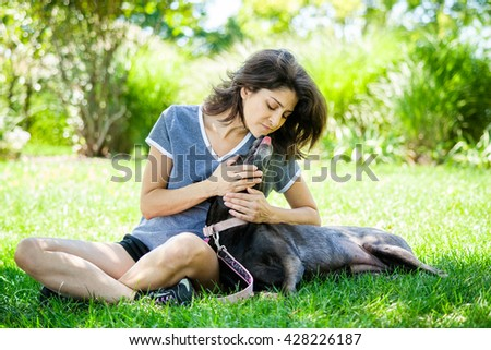 Middle aged woman affectionately holding her pet labrador retriever dog with dog licking her face at the park - stock photo