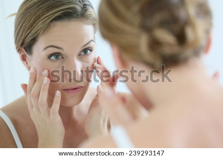 Middle-aged woman applying anti-aging cream - stock photo