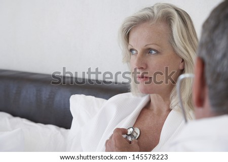 Middle aged woman being examined by doctor in bed at home - stock photo