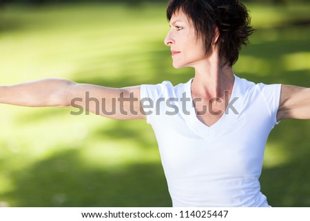 middle aged woman doing exercise outdoors - stock photo