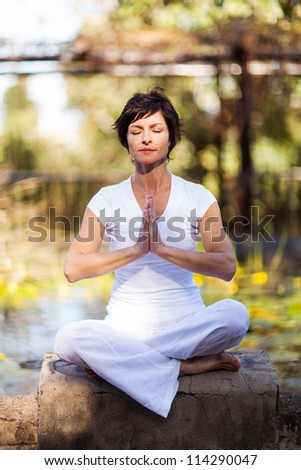 middle aged woman doing meditation by the pond - stock photo