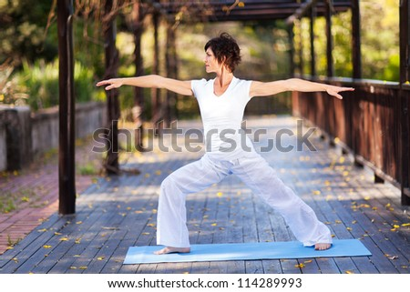 middle aged woman doing yoga outdoors - stock photo