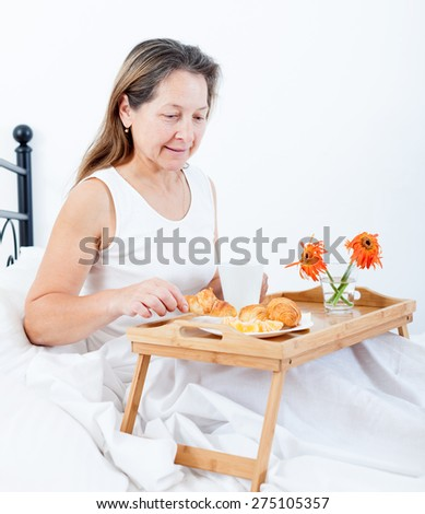 Middle-aged woman having breakfast in bed coffee with croissants.  - stock photo
