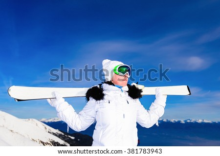middle-aged woman in a sports suit and skis in the mountains - stock photo