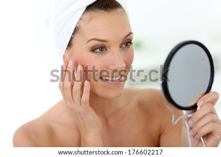 Middle-aged woman in bathroom looking at mirror - stock photo