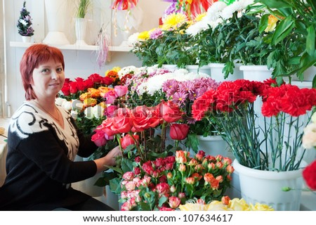 Middle-aged woman in  flower shop - stock photo