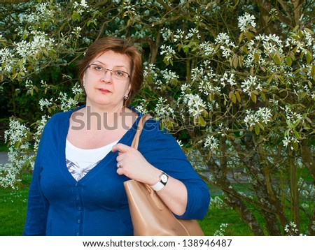 Middle-aged woman in the park in a blue sweater - stock photo