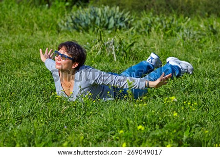 middle aged woman lying on a green grass  - stock photo