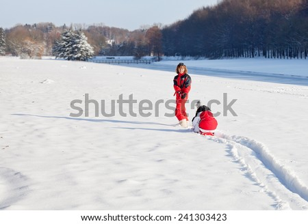 Middle aged woman pulling red sledge with her daughter across a snow field - stock photo