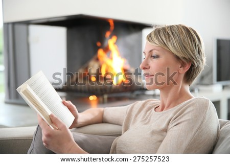 Middle-aged woman reading book by fireplace - stock photo