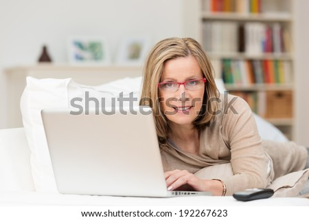 Middle-aged woman relaxing at home with her laptop computer lying on her stomach on a sofa smiling at the camera - stock photo