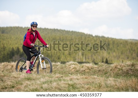 Middle aged woman riding bike  - stock photo