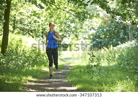 Middle Aged Woman Running In Countryside - stock photo