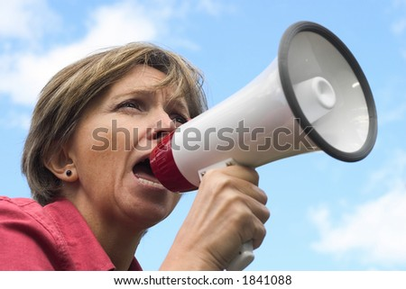 Middle-aged woman shouting through the megaphone. - stock photo