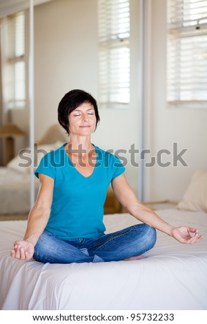 middle aged woman sitting on bed doing yoga meditation - stock photo