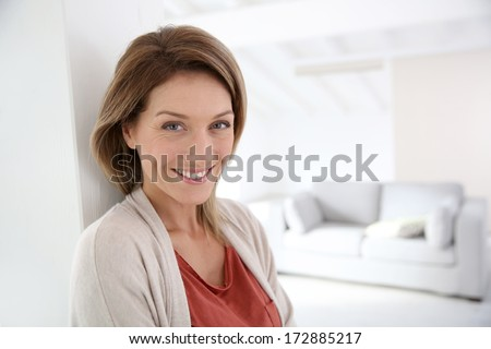 Middle-aged woman standing in modern home - stock photo