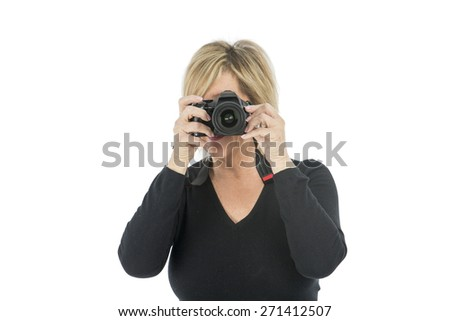 Middle aged woman taking a photograph with her camera against a white background - stock photo