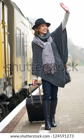 Middle aged woman waving on railway station platform - stock photo