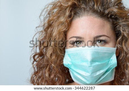 middle aged woman wearing a face mask outdoors as protection against an airborne virus or bacteria, head shot on grey - stock photo