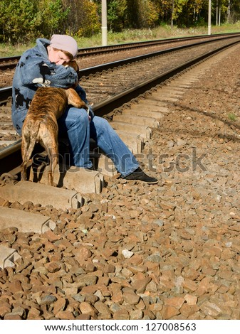 Middle-aged woman with a dog sitting on a railroad - stock photo