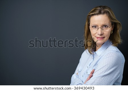 middle-aged woman with folded arms looking over her shoulder at the camera, with copy-space - stock photo