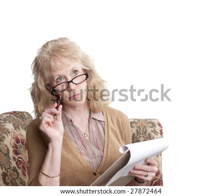middle-aged woman with glasses on, sitting on sofa with note pad looking perplexed,  isolated on white - stock photo