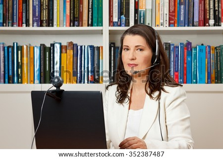 Middle aged woman with headset in front of her computer with webcam in a library, consultant, teacher, tutor, online course - stock photo