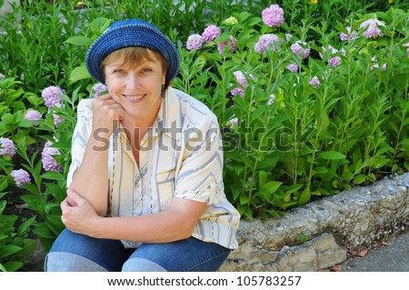 Middle-aged woman working in the garden - stock photo