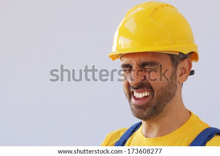Middle-aged workman wearing a safety helmet or hardhat screwing up his eyes in pain due to a migraine headache or injury over a grey studio background with copyspace - stock photo