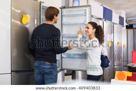 Middle class russian family couple choosing new refrigerator in hypermarket  - stock photo