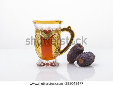 Middle eastern beverage and refreshment. Cup of black arabic tea and date fruits.  - stock photo
