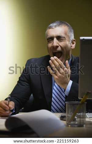 Middle Eastern businessman yawning at desk - stock photo