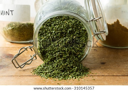 Middle Eastern cuisine: a jar of dried parsley with other herbs in the background. - stock photo