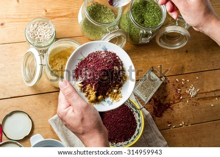Middle Eastern cuisine: chef mixing spices and herbs to give flavour to the food. On the plate are powdered ginger and garlic, and sumac. - stock photo