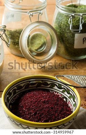 Middle Eastern cuisine: close-up on bowl of sumac, portrait orientation. Sumac powder is used in Arabic cuisine to add zest and flavour to dishes. Jars with dried parsley and mint in the background. - stock photo