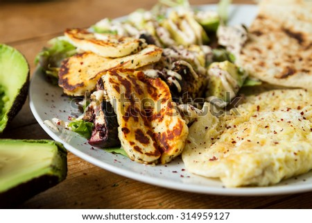 Middle Eastern cuisine: delicious plate of grilled halloumi cheese served with a lettuce and avocado salad, seasoned with sumac and other spices. - stock photo
