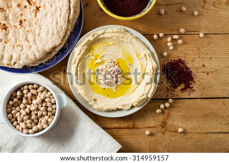 Middle Eastern cuisine: freshly made hummous, a spread made from chickpeas and seasoned with sumac and oil. Served with flat bread. - stock photo