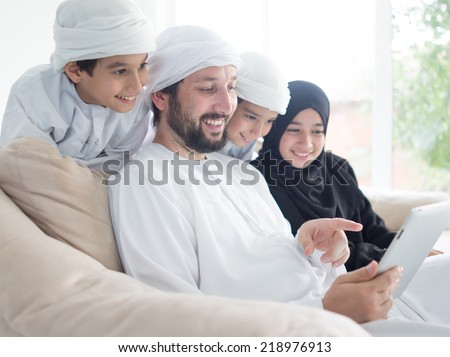 Middle eastern family at home on couch using tablet - stock photo